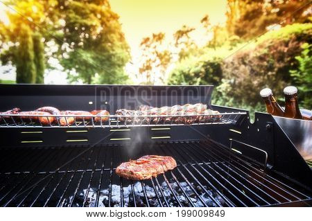 Meat steak cooking on barbecue grill for summer outdoor party. Food background with barbecue party
