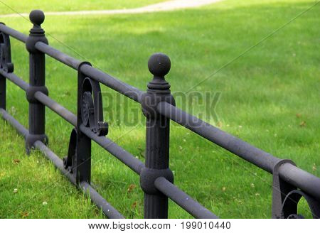 Black, wrought iron fencing with mown lawn beyond