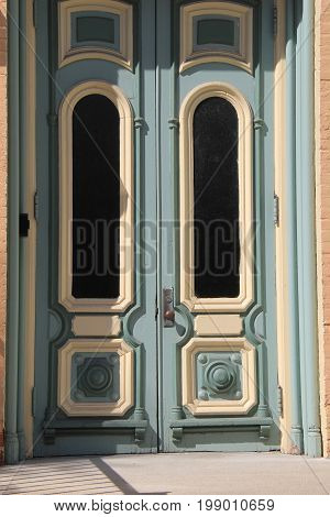 Old blue doors with peeling pain and ornate carvings at country home.
