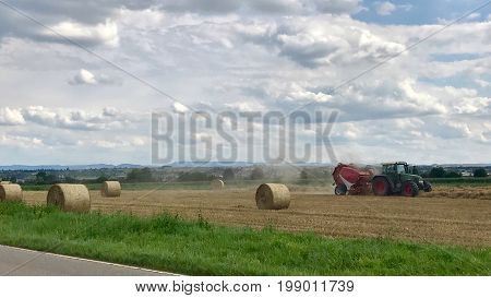 Tractor making hay bales on sunny summer day