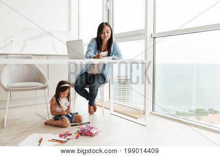 Photo of concentrated young woman write notes while her little daughter at home indoors sitting on floor.