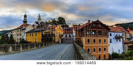 Beautiful sunset view of city of Murau with Mur River, houses and church in Tirol, Austria, Europe
