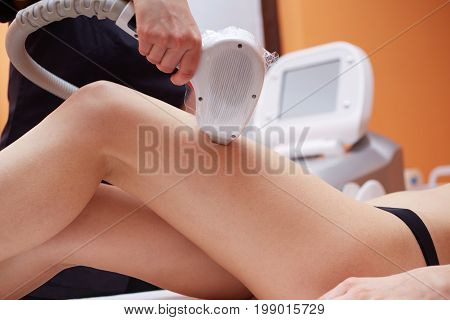 Beautician Removing Hair Of Young Woman's legs
