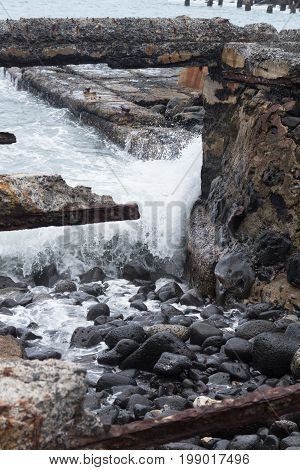 Waves crash on the rocks and ruins of an old abandoned sugarmill at Mahukona Beach Park on the Big Island of Hawaii.