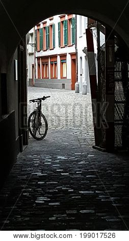 Lonesome bicycle in an arched alleyway on a cobblestone walkway in Switzerland.