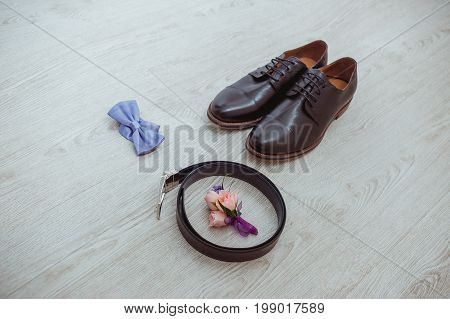 Boutonniere of the groom of a rose, a blue bow tie, brown shoes and a belt for the groom