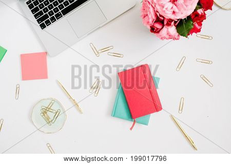 Flat lay home office desk. Female workspace with laptop pink and red roses bouquet golden accessories red and mint diary on white background. Top view feminine background.