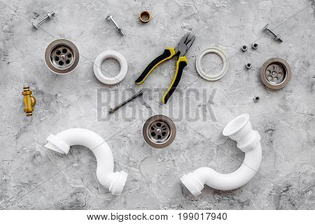Plumber tools on grey stone background top view.