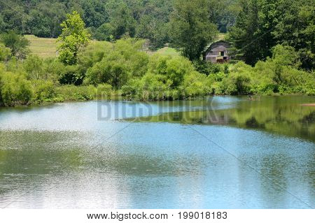 a barn on the banks of a small lake reflecting the sky