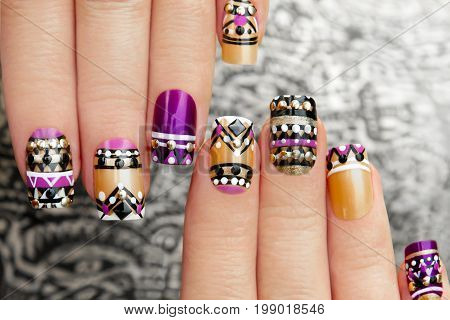 Manicure with colorful ethnic design with rhinestones on female hand close up on colorful background.
