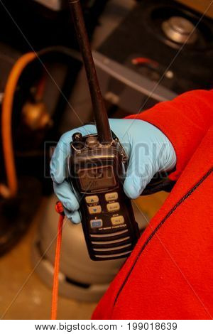 VHF radio in a hand, wearing a protective glove