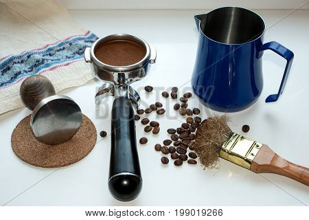 Filter holder for coffee machines with coffee tamper and pitcher on coffee beans.