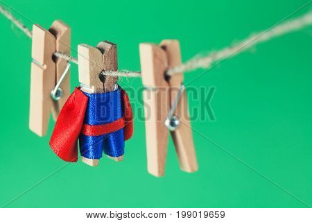 Brave superhero wooden clothespins. Team leader character in blue suit red cape. green background, selective focus.