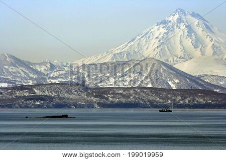 Avacha Bay with the submarine and fishing vessels on the background of the volcano. Kamchatka.