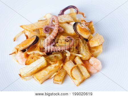 Fried potato cuttlefish octopus mussels shrimp. White plate background, up view
