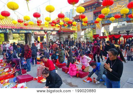 HONG KONG, CHINA - JANUARY 22, 2017: Crowd of people praying over their knees in a red soft pad inside of Wong Tai Sin Buddhist Temple to pray, in Hong Kong, China.