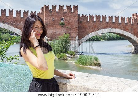Portrait of a young woman talking on phone. In the background the medieval stone bridge Scaligero built in 14th century near Castelvecchio Verona (Italy). Shallow DOF.
