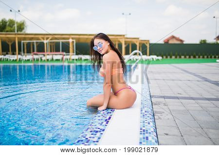 Sexy Young Woman Sitting On The Edge Of A Swimming Pool, Wearing Bikini While On Vacations In A Sunn