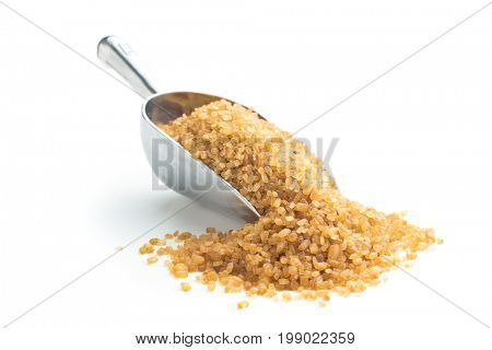 Brown cane sugar in scoop isolated on white background. crystalline brown sugar.