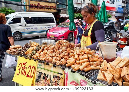 BANGKOK, THAILAND - JULY 30, 2017: Unknown vendor prepare food at a street side restaurant. More than 16.000 people are registered as street vendors in Thailand