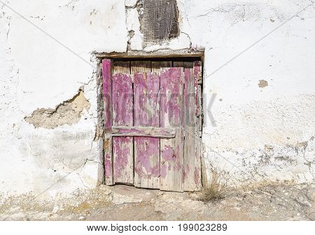 ancient wooden door on a cement white wall