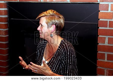 Profile of middle-age woman gesturing while seriously talking to someone else.