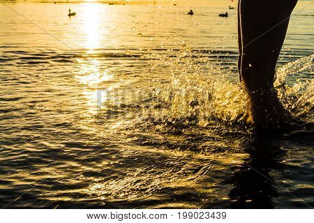 A Splash Of Water Created By The Boy's Foot, The Orange Trace Of The Scorching Sun