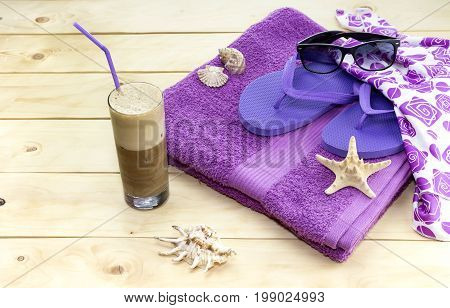 Towel, flip flops, seashell, sunglasses and a glass of cold coffee on a wooden table close-up
