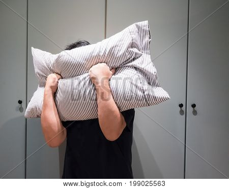 Depressed Man Covering His Face With Pillow And Screaming In Anger In His Room