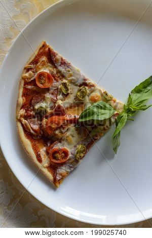 Two Slices Of Pizza On White Plate At Restaurant Table. Close Up