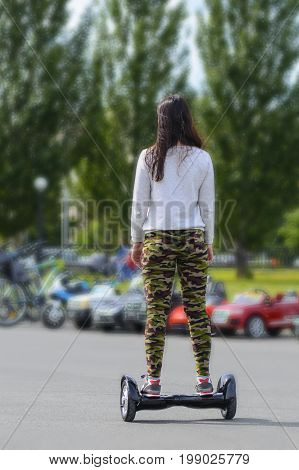 Young beautiful woman in sports wear riding gyro scooter on green urban scene outdoors. Electronic scooter personal portable eco transport