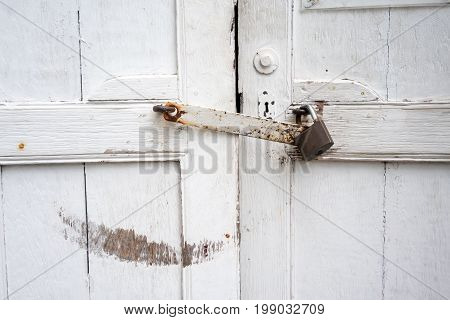 Antique closed door painted with white and locked with rusty latch and padlock for vintage background