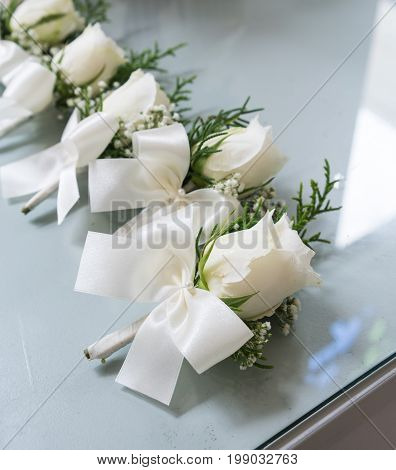 White roses boutonniere with white bow tie ribbon groomsmen on glass table in shadow of light through the window. Selective focus for wedding boutonniere idea.