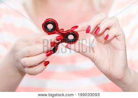 A girl is holding a popular toy metallic red fidget spinner in her hands. Stress relief. Anti stress and relaxation fidgets, spinner for tired people. Girl playing with a fidget spinner.