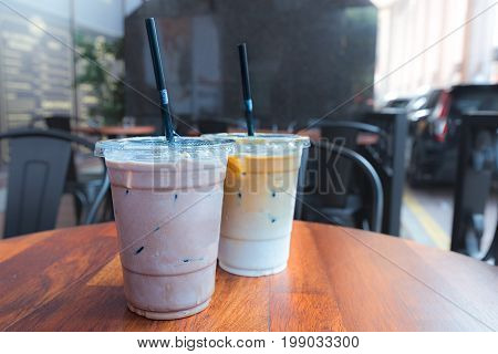 Iced Mocha And Iced Latte Coffee Drinks In Clear Plastic Cups With Straws.