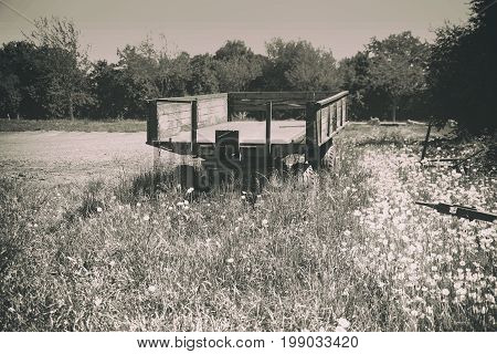 An old tractor trailer stands on a wild meadow and is overgrown.