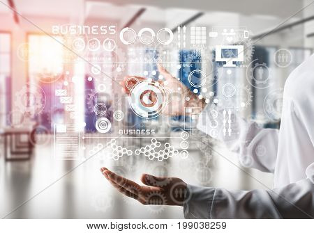 Closeup of business woman in shirt with business interface and media icons in her hands. Sunlight and office view on background. Mixed media.