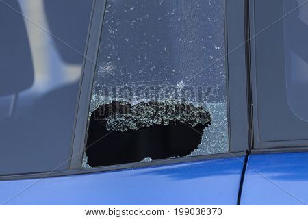 Smashed rear car door window from vehicle burglary.