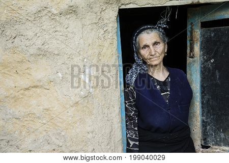 Gilan Province- IRAN-May 10 2017 Portrait of an Iranian woman in traditional cloth at vintage doorway