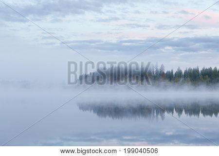 Calm foggy lake scape summer night at Finland