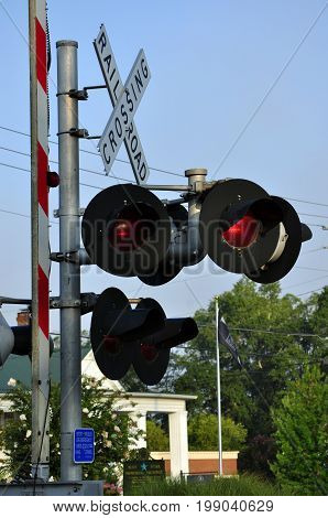 Railroad crossing signal standing sentinel at the intersection of a railroad track and state highway.