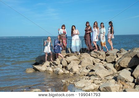 Group of young womens standing together at a beach on a summer day. Happy young people enjoying a day at beach.