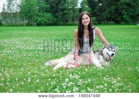 Beautiful happy young woman playing with funny husky dog outdoors at park