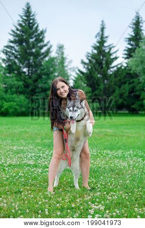 young woman playing with funny husky dog outdoors at park