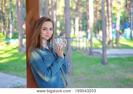 Beautiful young woman , drinking takeaway coffee from cup, outdoors in summer. , space for text, horizontal format image