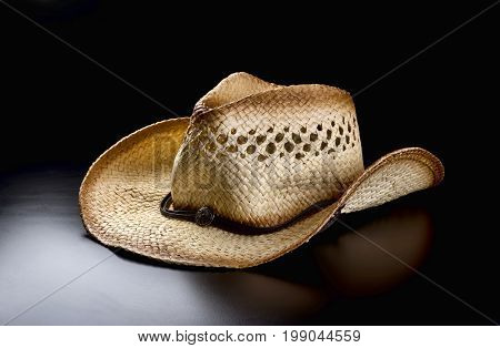 Old straw cowboy hat on black background..
