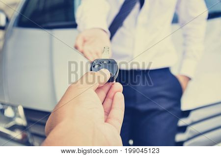 Hand giving car key to a man with car background - vintage (retro) style color effect