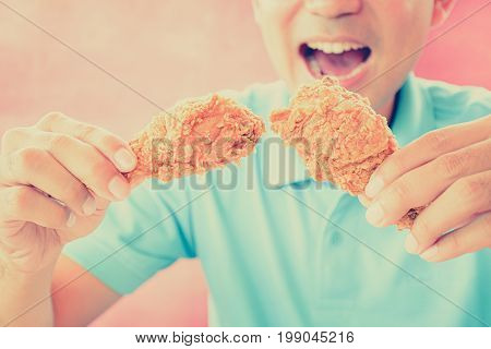 A man with opening mouth about to eat deep fried chicken legs or drumsticks -vintage (retro) style color effect