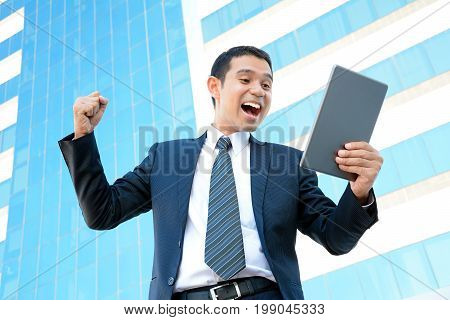 Businessman yelling & raising his fist while looking at tablet pc