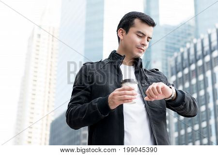 Handsome man in casual clothes checking for the time waiting for someone in the city
